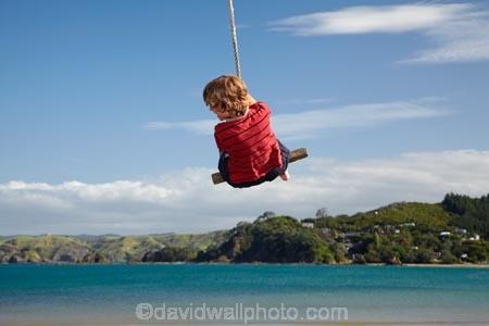 Girl on rope swing, Oakura Bay, Northland, North Island