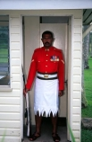 guard;guarding;stand;standing;uniform;red;white;shirt;belt;medal;medals;doorway;headquarters