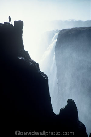 on-the-edge;Victoria-Falls;Zimbabwe;Zambia;southern-Africa;african;silhouette;silhouettes;waterfall;waterfalls;africa;zambezi-river;zambesi;zambeze;rivers;power;alone;solo;top;atop;cliff;cliffs;bluff;bluffs;danger;dangerous;high;person;people;mist;misty;adventure;excite;exciting;heights