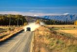 mountain;mountains;range;ranges;road;road;loose-metal;shingle;gravel;unsealed;dust;dustcloud;vehicle;farm;farmland;farm-vehicle;grass;paddocks;fields;meadows