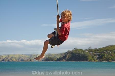 Boy on rope swing, Oakura Bay, Northland, North Island