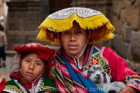 Indigenous Peruvian Woman And Young Girl In Traditional Costume And Baby Alpaca