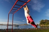action;activity;caucasian;child;Child-Playing;childhood;children;excercise;excercising;fun;girl;girls;gymnastics;hang;hanging;jungle-gym;Karitane;Monkey-Bars;New-Zealand;Otago;outdoors;park;parks;people;person;play;playground;playgrounds;playing;plays;recreation-leisure;South-Island;swing;swinging;young